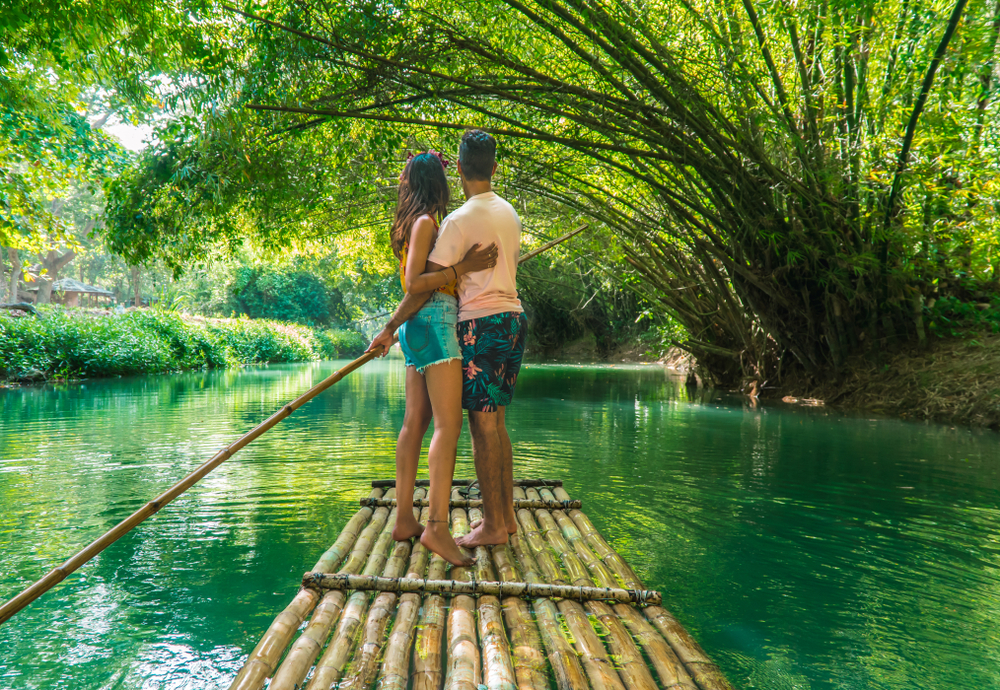 Happy couple hugging and standing on bamboo raft, whilst on cruise along Martha Brae
