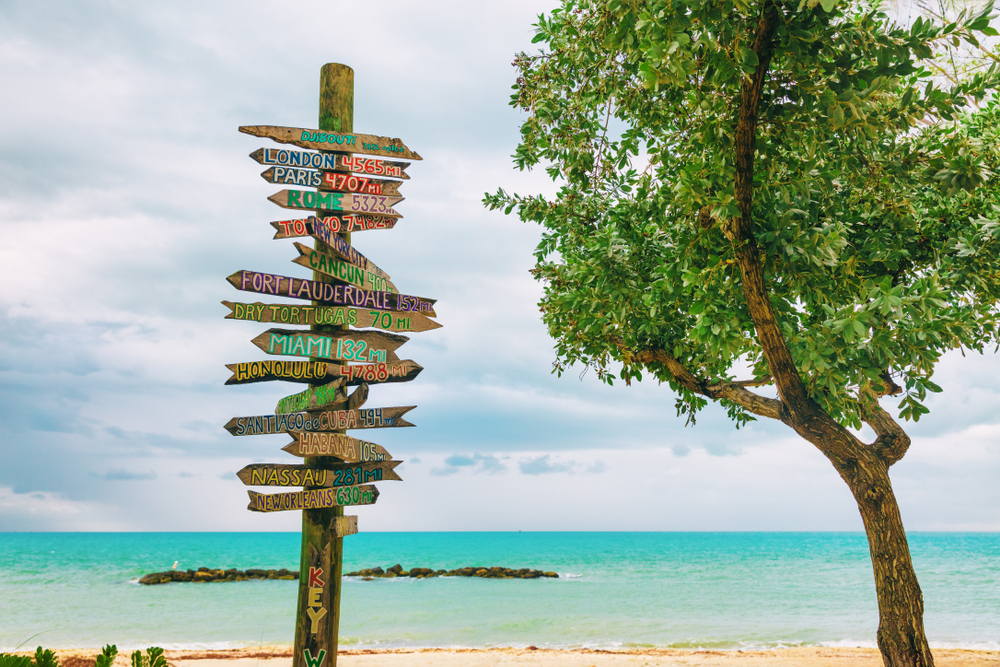 Key West popular tourist attraction on Florida Zachary beach, wooden direction signs signaling distances which way to famous places travel the world.