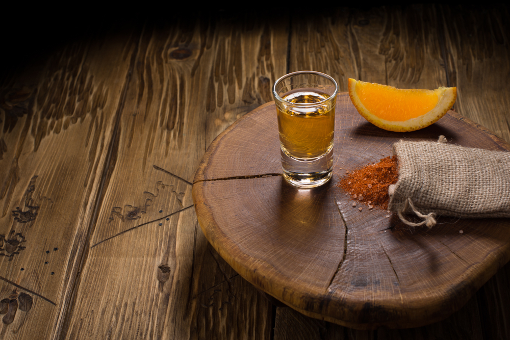Mezcal - traditional Mexican drink with orange slices, chili pepper and worm salt on a old wooden table.