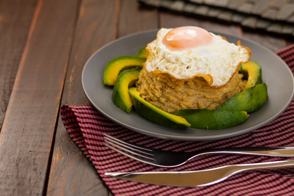 Green plantains mashed with fried egg and avocado, on wooden table. Delicious Mangu traditional Dominican food.