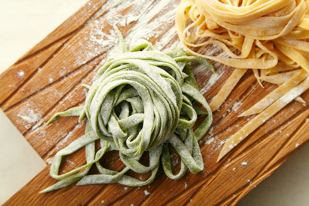 Two types of handmade italian tagliatelle pasta: classical one and green one with spinach on wooden cutting board