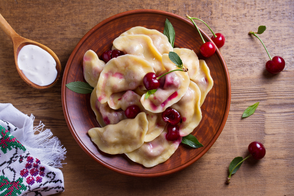 Dumplings, filled with cherries, berries. Pierogi, varenyky, vareniki, pyrohy - dumplings with filling, popular dish in many countries. View from above, top studio shot
