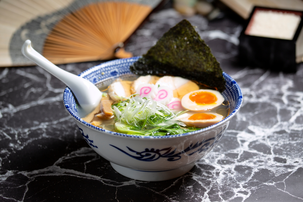 Traditional japanese shio Ramen noodle with chicken and narutomaki served on blue bowl photo from above view on marble top