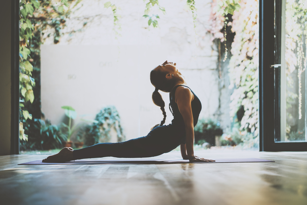 Portrait of gorgeous young woman practicing yoga indoor. Beautiful girl practice cobra asana in class.Calmness and relax, female happiness.Horizontal, blurred background